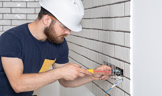 Operaio edile elettricista con la barba in tuta durante l'installazione delle prese. .
