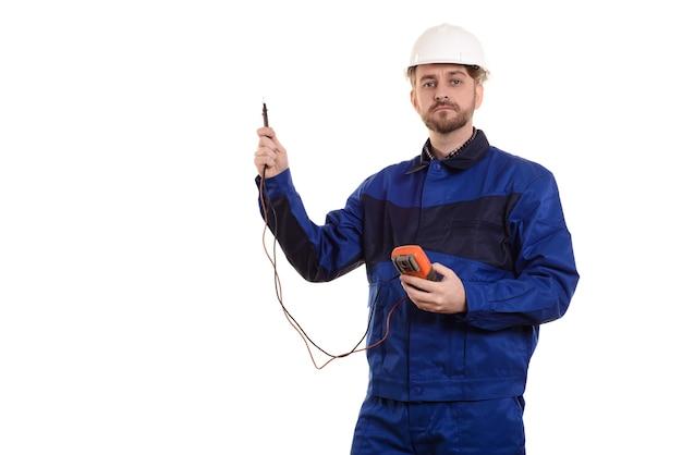 Ingegnere elettricista in casco e uniforme con strumento tester