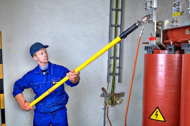L'ingegnere elettricista impone il collegamento di terra al trasformatore di potenza riduttore, utilizzando apparecchiature di messa a terra, stick di scarica e cavi di pinze di messa a terra.