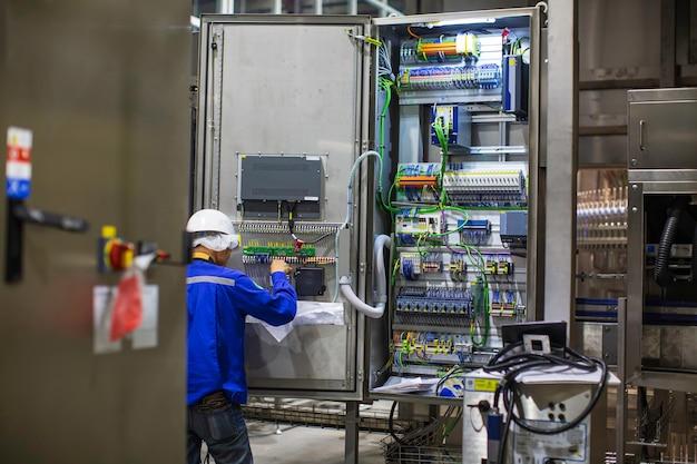 L'ingegnere elettricista testa le installazioni e i cavi della macchina di controllo della scatola elettrica all'interno della fabbrica