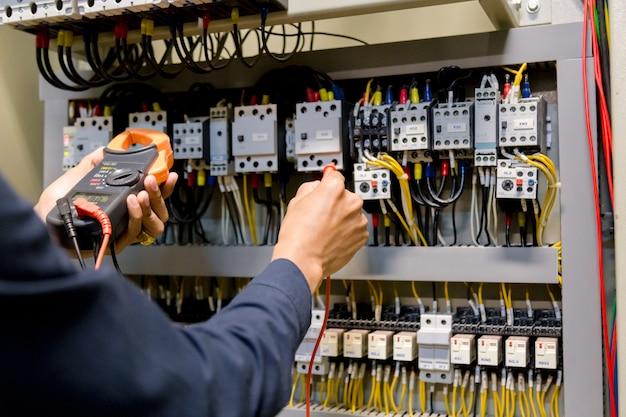 Tester di lavoro dell'ingegnere dell'elettricista che misura tensione e corrente della linea elettrica di potere nel controllo elettricamente del gabinetto. Foto Premium