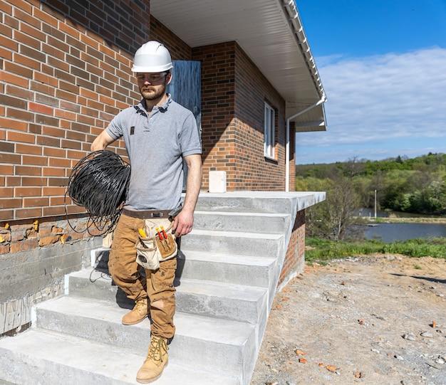 Un elettricista esamina un cantiere mentre tiene in mano un cavo elettrico in cantiere.