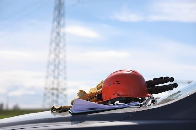 Un elettricista nei campi vicino alla linea di trasmissione di potenza. l'elettricista gestisce il processo di costruzione delle linee elettriche. il meccanico in un casco e guanti speciali di forma riflettente sul lavoro.