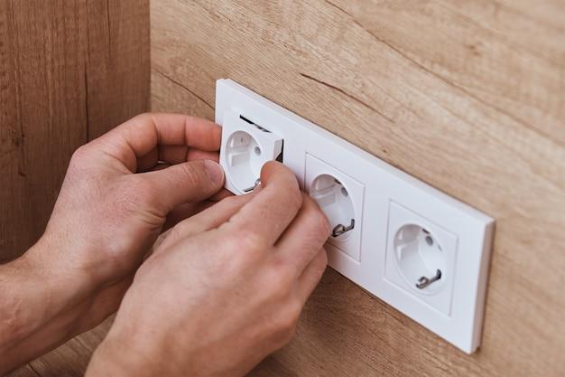 Elettricista mani montaggio presa nel muro