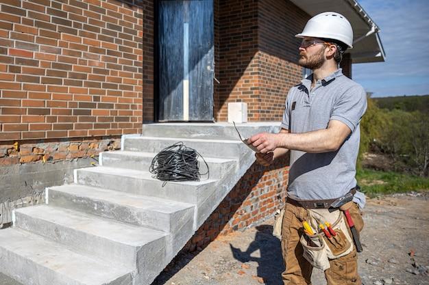 Un elettricista tiene in mano un disegno di costruzione e ispeziona un oggetto funzionante.