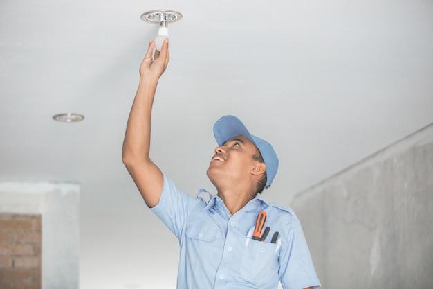 Elettricista che installa lampadina nel downlight