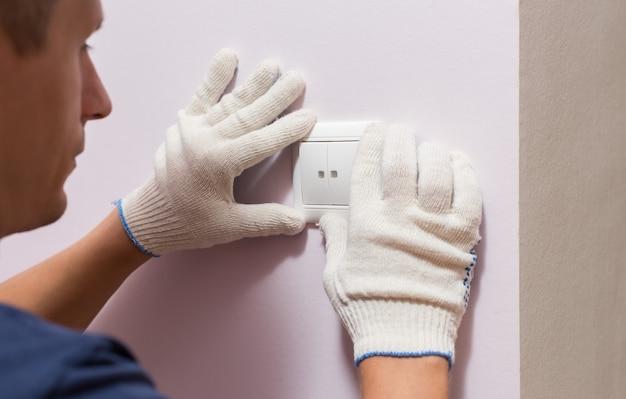 Elettricista che installa interruttore della luce, foto ravvicinata.