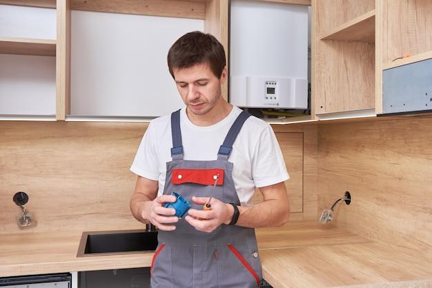 Elettricista che installa una spina della presa in cucina. concetto di ristrutturazione