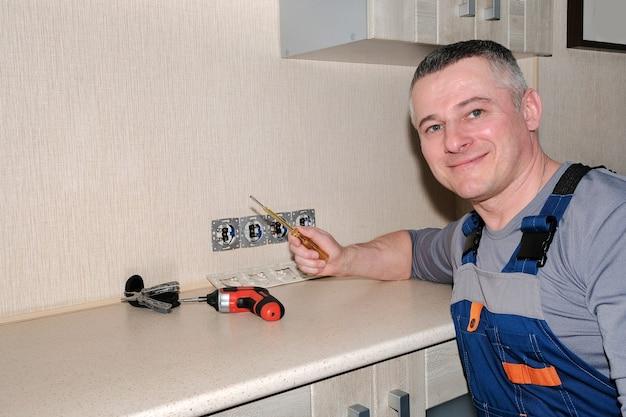 Un elettricista installa prese elettriche in cucina. strumenti in mano. design moderno.