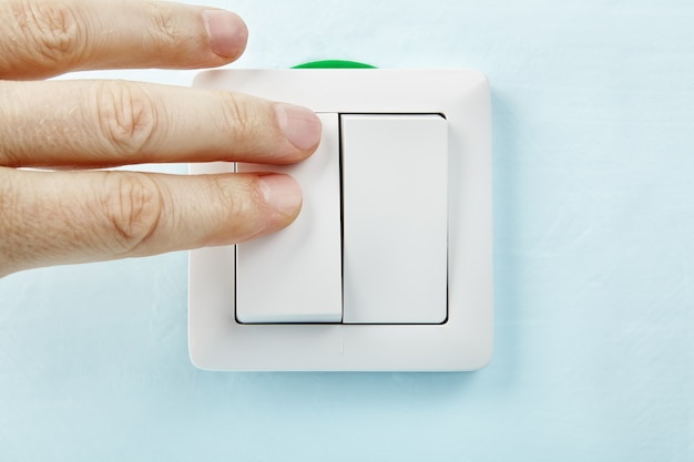 L'elettricista sta premendo il pulsante del nuovo interruttore della luce standard europeo, installazione elettrica.