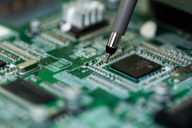 Un elettricista misura la tensione mentre ripara un televisore con lsd in un centro di assistenza