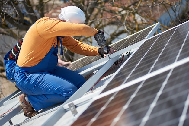 Elettricista montaggio pannello solare sul tetto di una casa moderna