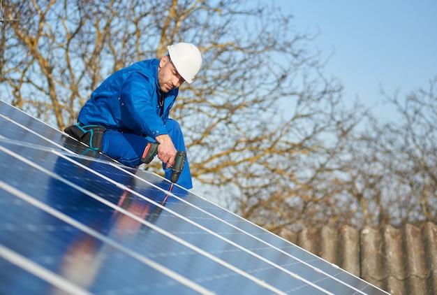Elettricista che monta pannello solare sul tetto della casa moderna