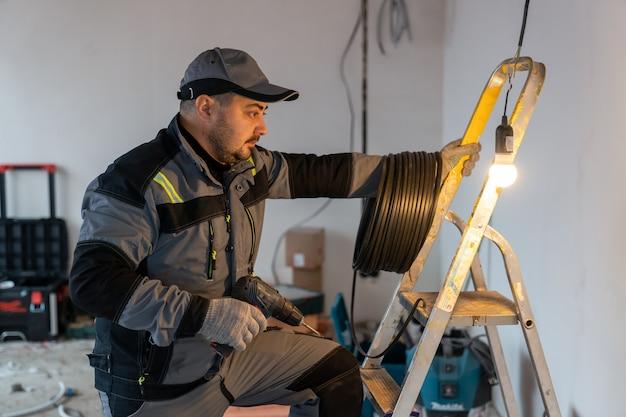 Un elettricista in tuta con una bobina di fili e un trapano sale su una scala accanto a una lampadina accesa