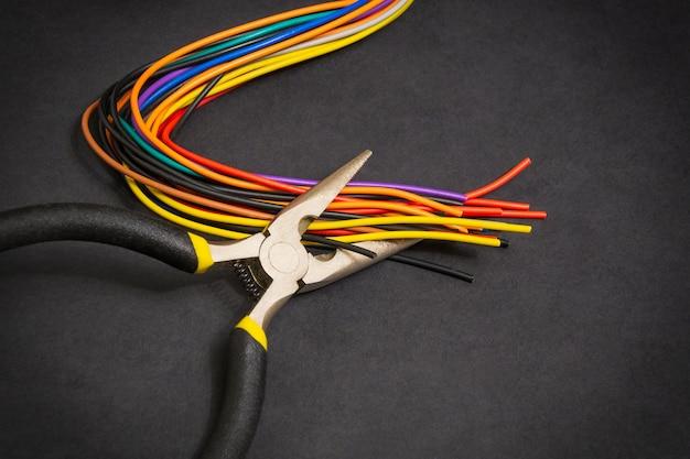 Le pinze e il filo dell'elettricista su sfondo scuro per la riparazione di sistemi o comunicazioni energizzati
