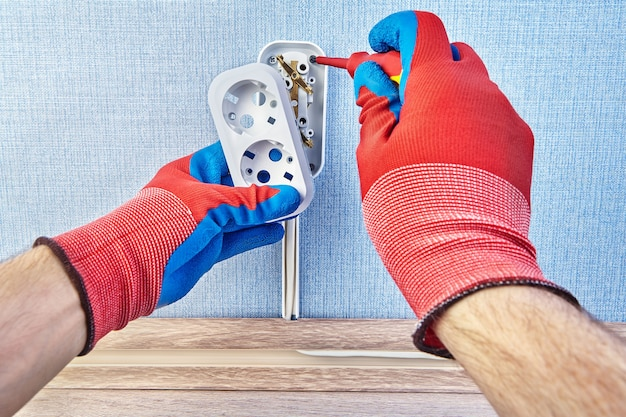 Elettricista in guanti protettivi sta torcendo la vite sotto la scatola del pattress della nuova presa a muro in euro.