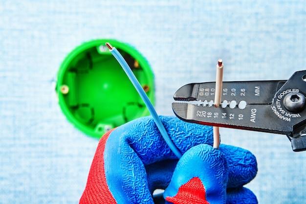 Elettricista in guanti protettivi toglie il filo con una taglierina spelafili durante l'installazione della scatola elettrica.
