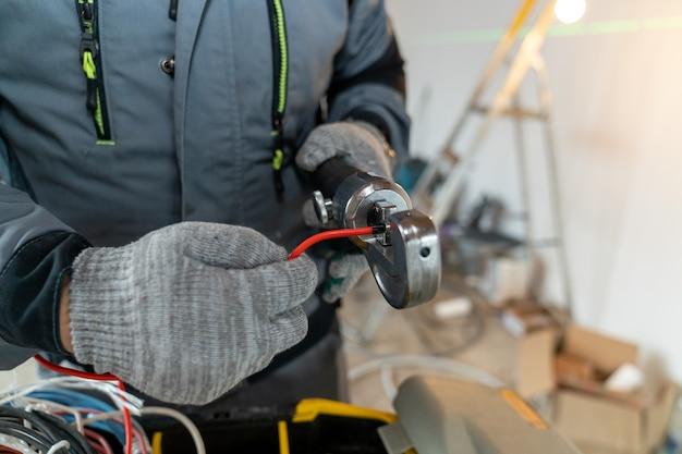 L'elettricista indossa i guanti e lavora i bordi dei fili con uno strumento speciale