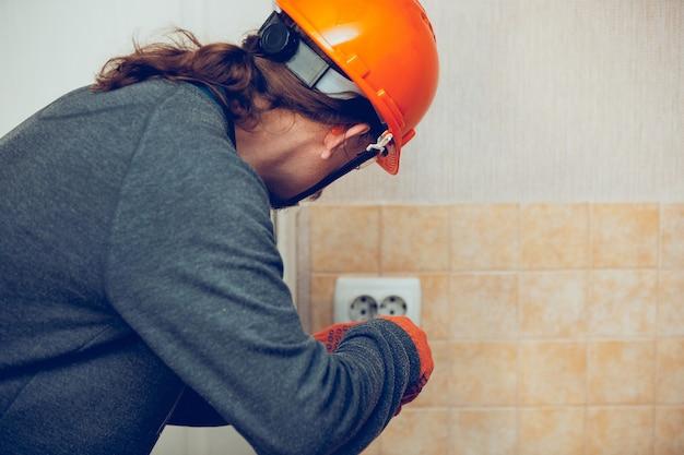 L'elettricista ripara una presa a muro a casa o in ufficio. primo piano dell'uomo in abiti da lavoro che ripara una presa elettrica. concetto pericoloso, alta tensione, rischio, sostituzione del cablaggio, occupazione del tecnico.
