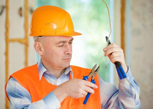 Elettricista che ripara il cablaggio del soffitto in casa