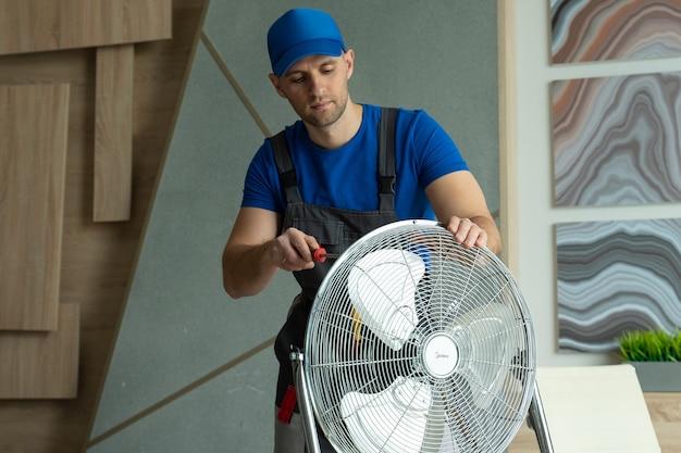 Un elettricista ripara la riparazione della ventola di raffreddamento delle apparecchiature nella stanza