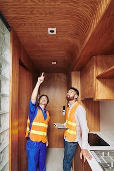 Elettricista che mostra prese di luce che ha installato nel soffitto in legno nella zona cucina al caposquadra con tavoletta digitale nelle mani