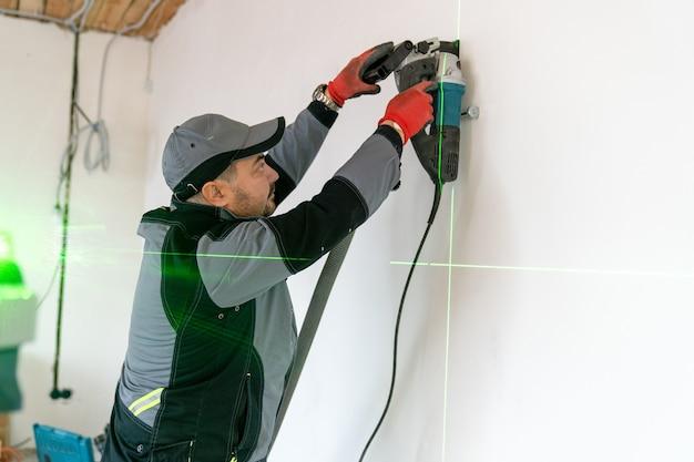 L'elettricista ha acceso il puntatore laser e ha realizzato un fossato nel muro per il cablaggio con uno strumento speciale