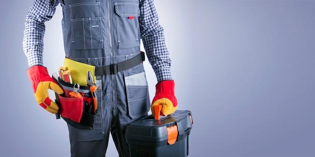 Elettricista con strumenti elettrici su sfondo grigio chiaro con posto per il testo. banner di lavoro tuttofare.