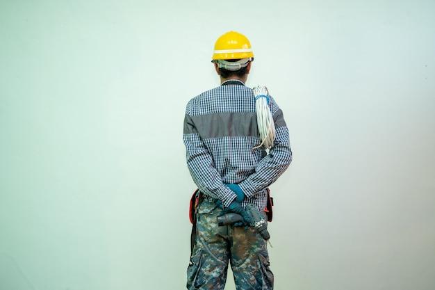 Elettricista con un casco di sicurezza e un mucchio di cavi all'interno.