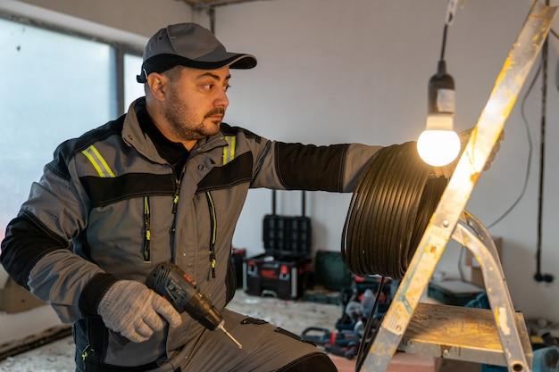 Un elettricista con un cacciavite e una bobina di filo vuole salire una scala