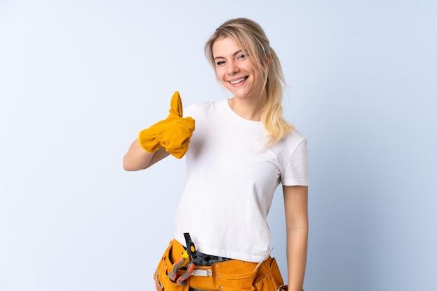 La donna dell'elettricista sopra la parete blu isolata che dà i pollici aumenta il gesto