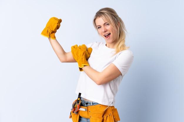 Donna dell'elettricista sopra la parete blu isolata che fa forte gesto