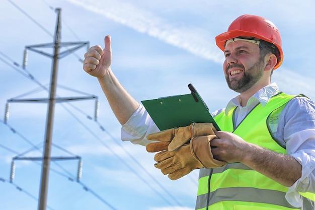 Elettricista che lavora in un casco indossando guanti in piedi in un campo