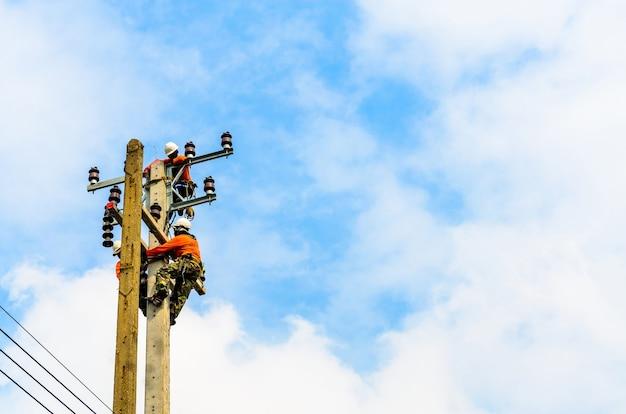 Gli elettricisti stanno salendo sui pali elettrici per installare e riparare le linee elettriche.