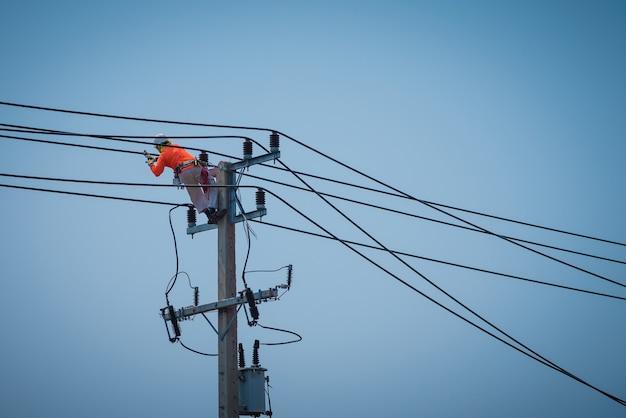 Gli elettricisti si arrampicano sui pali elettrici per installare e riparare le linee elettriche