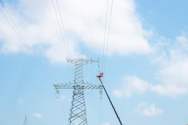 Gli elettricisti sono impegnati nella manutenzione delle linee elettriche contro un cielo blu