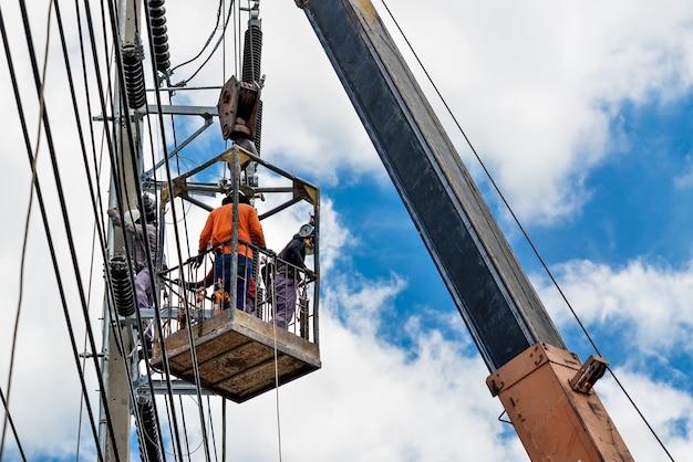 Gli elettricisti sono in un cesto su un palo elettrico per installare e riparare i cavi.