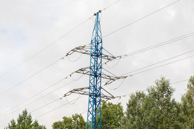 Pilone ad alta tensione di elettricità che si staglia contro il cielo nuvoloso