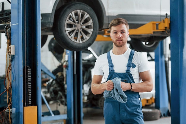 Elettricità e tecnologia. l'impiegato con l'uniforme di colore blu lavora nel salone dell'automobile.