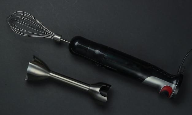 Kit frullatore elettrico a immersione su sfondo nero. vista dall'alto