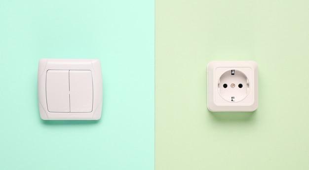 Presa elettrica, interruttore su uno sfondo pastello. vista dall'alto, minimalismo