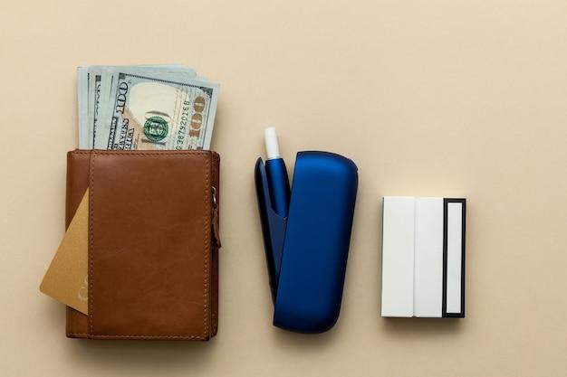 Portafoglio elettronico marrone sigaretta iqos blu con soldi su sfondo beige
