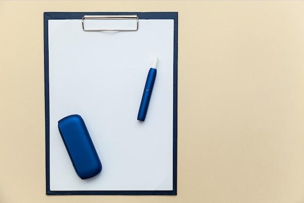 Cartella elettronica per sigarette iqos blu con clip per fogli di carta a4 su fondo beige
