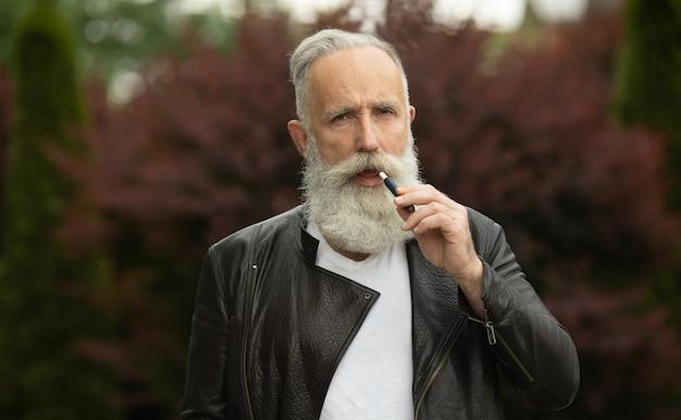 Tecnologia sigaretta elettronica. sistema iqos di tabacco. primo piano di un uomo anziano barbuto che fuma una sigaretta ibrida elettrica con un cuscinetto di riscaldamento.