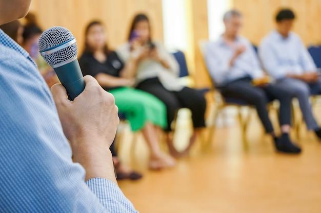 Il dispositivo elettronico sulla mano asiatica riproduce i social media nella sala riunioni con le persone sfocate dietro