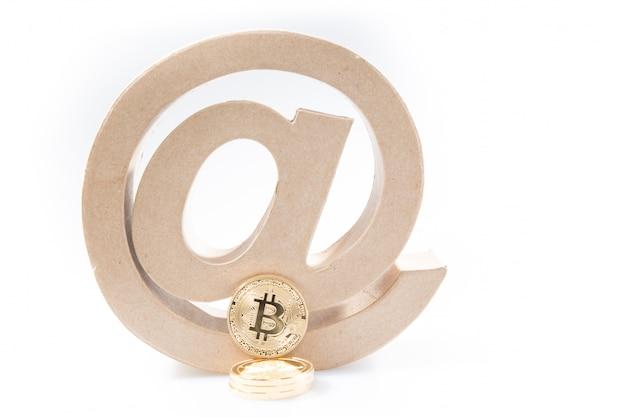 Simbolo di concetto di moneta elettronica con un arroba e bitcoin dorato per attività bancaria netta