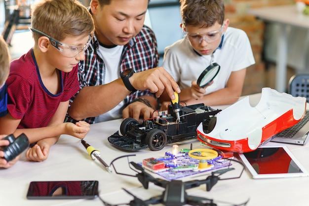 Insegnante di ingegneria elettronica con giovani studenti europei che collaborano con un modello di auto radiocomandato. saldatura di fili e circuiti, esperimenti fisici.