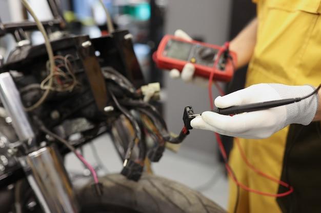 Maestro del servizio di riparazione elettronica che utilizza un tester multimetro per determinare la parte problematica