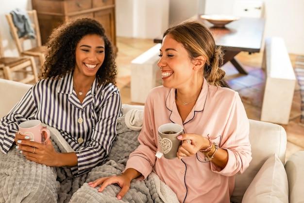 Eleganza, bellezza e felicità: le giovani donne multirazziali si accoppiano divertendosi indossando il pigiama seduto sul divano a bere una tazza di tè.