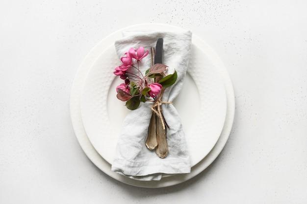 Regolazione romantica della tavola di eleganza con i fiori di melo su bianco.